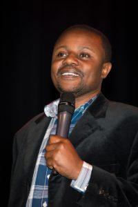 Arnold Muwonge speaking on stage